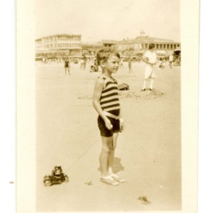 William Gaddis as a young boy at the beach, pulling a toy car