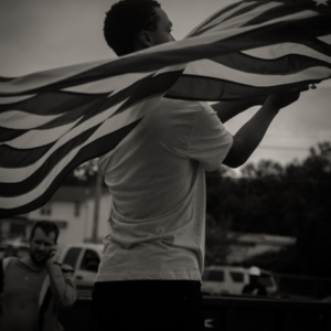 Protester waves an American flag at the Quick Trip on the corner of W. Florissant